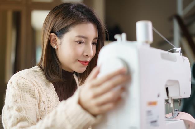 Szczęśliwa kobieta cieszy się pracę na szwalnej maszynie.