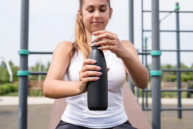 Szczęśliwa kobieta ćwicząca na boisku sportowym w słoneczny letni dzień, pijąca wodę z butelki
