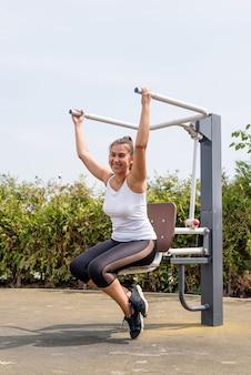 Szczęśliwa kobieta ćwicząca na boisku sportowym w słoneczny letni dzień