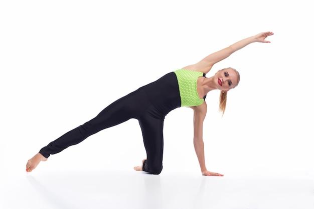 Szczęśliwa kobieta ćwiczeń w studio uśmiecha się radośnie podczas rozciągania