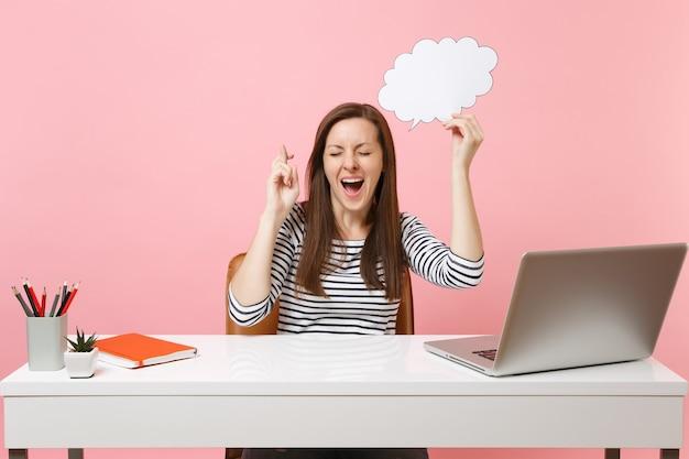 Szczęśliwa kobieta czeka na wyjątkowy moment trzymając skrzyżowane palce przytrzymaj puste puste powiedz chmura dymek pracuje w biurze z laptopem pc na białym tle na różowym tle. osiągnięcie kariery biznesowej. skopiuj miejsce.