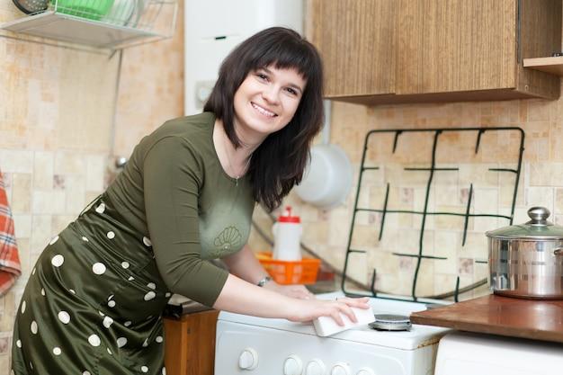 Szczęśliwa kobieta czyści kuchenkę gazową
