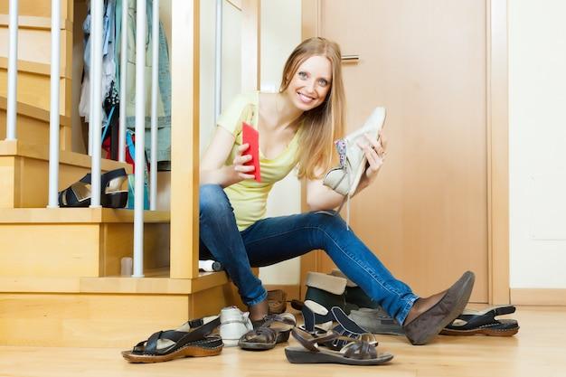 Szczęśliwa kobieta czyszczenia obuwia