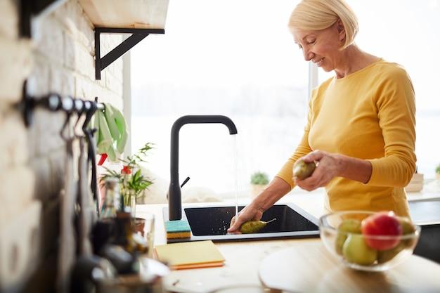 Szczęśliwa kobieta czyszczenia owoców