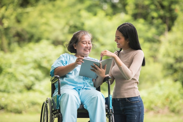Szczęśliwa kobieta czyta książkę z jej córką przy parkiem w wózku inwalidzkim