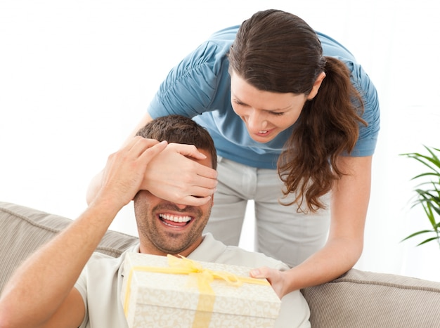 Szczęśliwa kobieta daje teraźniejszości jej mąż w żywym pokoju