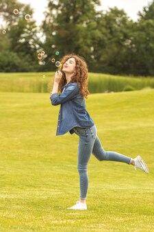 Szczęśliwa kobieta dmuchająca bańki w parku