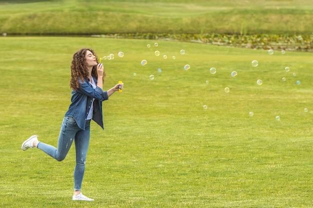 Szczęśliwa kobieta dmuchająca bańki w zielonym parku