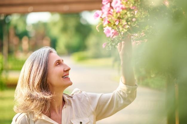 Szczęśliwa kobieta dotyka kwiatów w parku