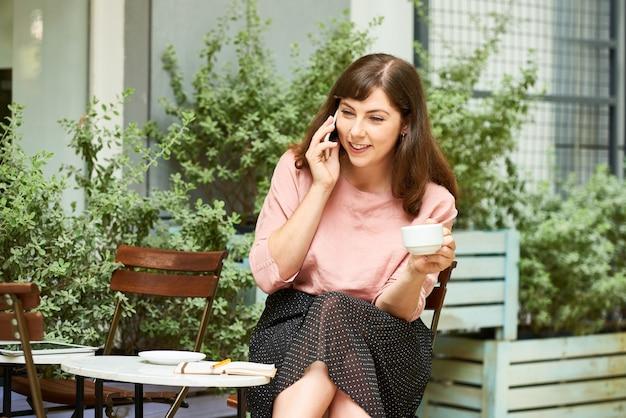 Szczęśliwa kobieta dzwoniąca do swojego przyjaciela