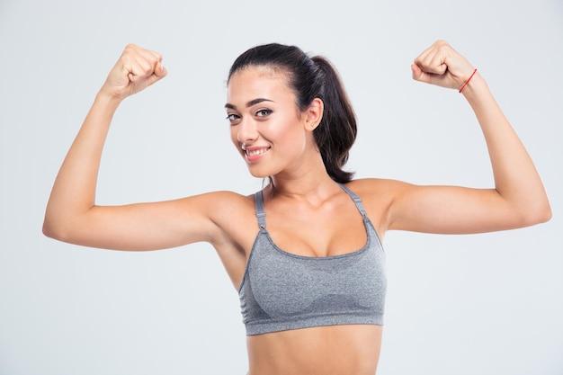 Szczęśliwa kobieta fitness pokazując bicepsy na białym tle na białej ścianie i patrząc z przodu