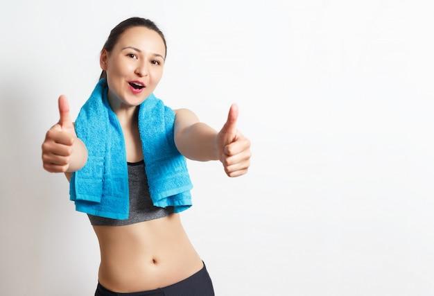 Szczęśliwa kobieta fitness pokazuje kciuk do góry znak.