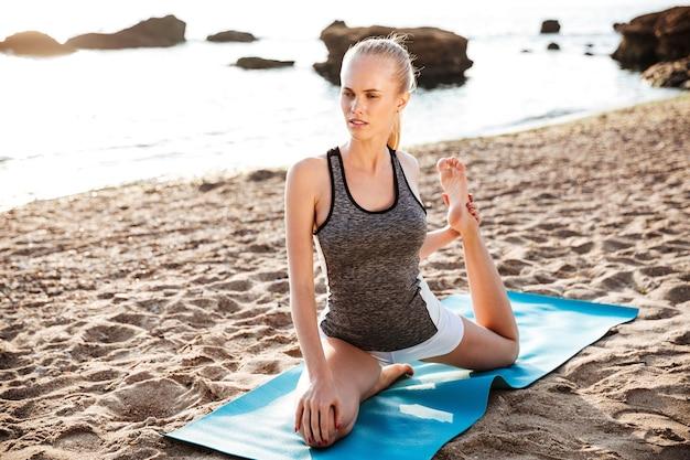 Szczęśliwa kobieta fitness robi ćwiczenia rozciągające na plaży