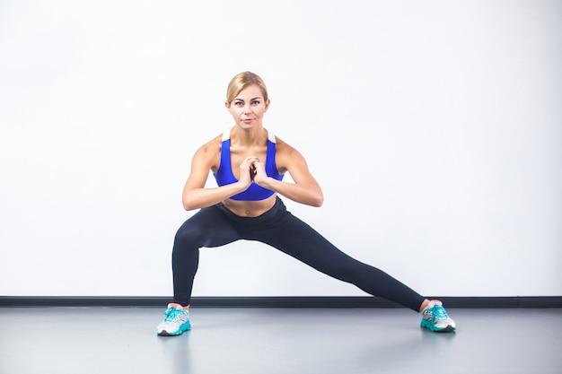 Szczęśliwa kobieta fitness robi odcinek ćwiczeń, patrząc na kamery. zdjęcia studyjne