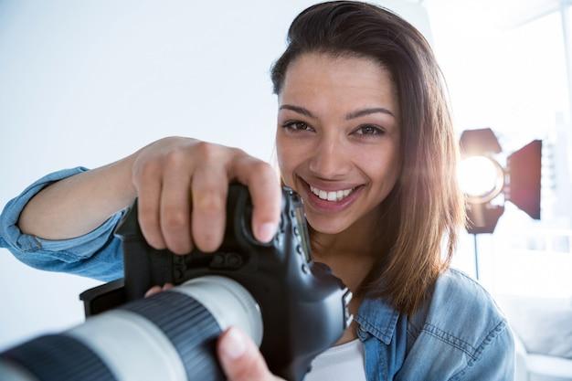 Szczęśliwa kobieta fotograf stojący w studio