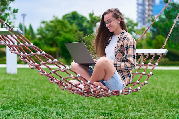 Szczęśliwa kobieta freelancer relaks na hamaku