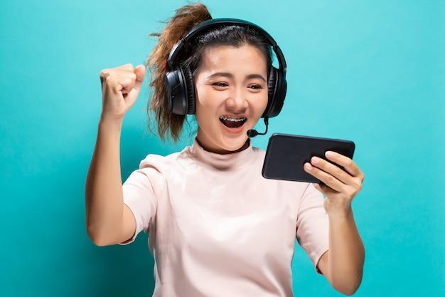 Szczęśliwa kobieta gra do gry ze smartfona