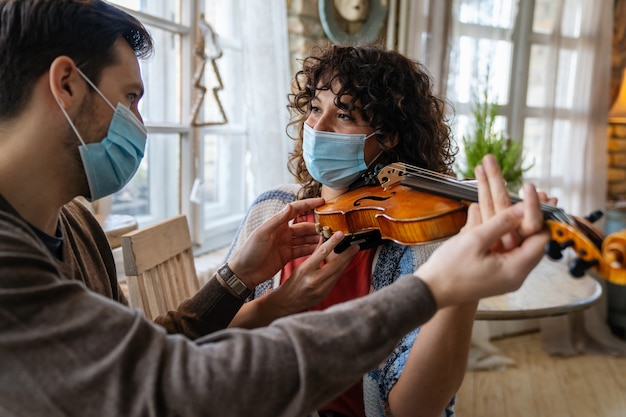 Szczęśliwa kobieta gra na skrzypcach zgodnie z instrukcjami męskiego nauczyciela muzyki w masce podczas koronawirusa w domu
