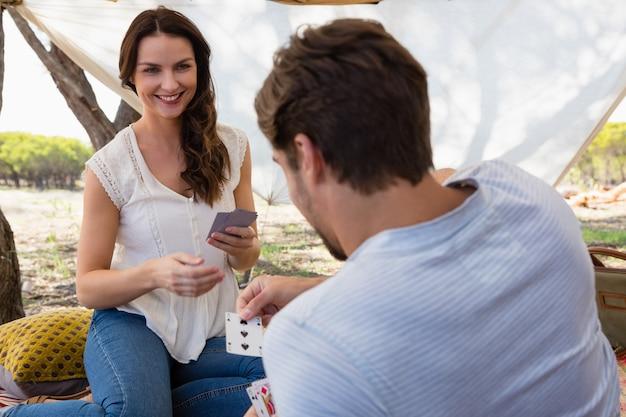 Szczęśliwa kobieta gra w karty z mężczyzną