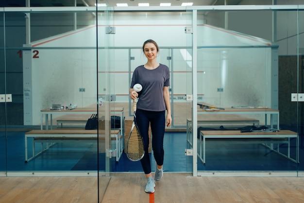 Szczęśliwa kobieta gracz z rakietą do squasha w szatni. dziewczyna na treningu gier, aktywne hobby sportowe, sprawny trening dla zdrowego stylu życia