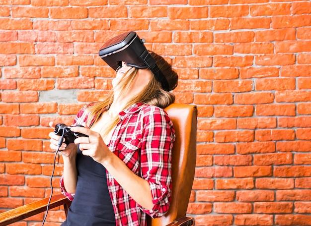 Szczęśliwa kobieta grając w gry z zestawem słuchawkowym wirtualnej rzeczywistości.