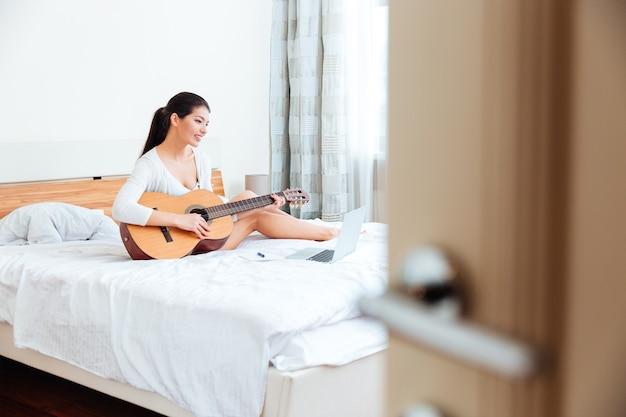 Szczęśliwa kobieta grająca płyty na gitarze obsługiwanej przez komputer przenośny na łóżku w domu