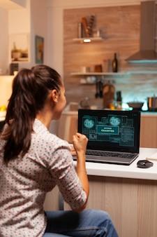 Szczęśliwa kobieta haker po złamaniu zapory rządowej i uzyskaniu dostępu. programista piszący niebezpieczne złośliwe oprogramowanie do cyberataków przy użyciu wydajnego laptopa o północy.