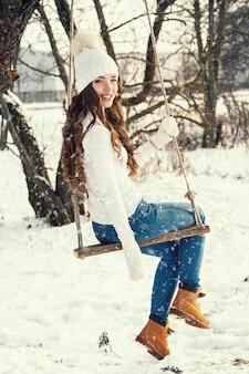 Szczęśliwa kobieta i arkana huśtamy się w zima krajobrazie