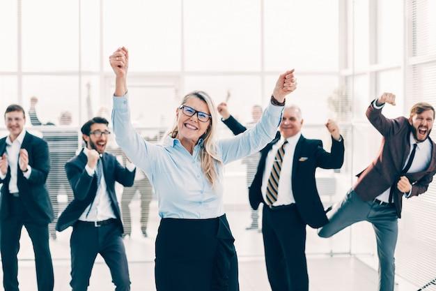 Szczęśliwa kobieta i grupa pracowników stojących w biurze. koncepcja sukcesu