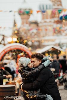 Szczęśliwa kobieta i mężczyzna na jarmarku bożonarodzeniowym