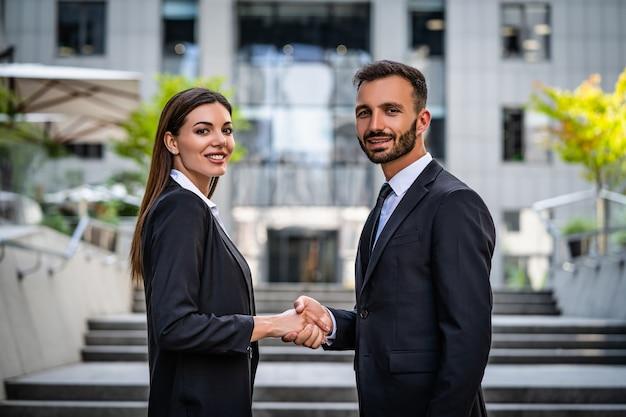 Szczęśliwa kobieta i mężczyzna w garniturach uścisk dłoni w pobliżu centrum biznesowego