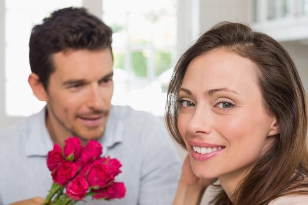 Szczęśliwa kobieta i mężczyzna z kwiatami w domu