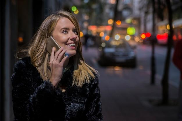 Szczęśliwa kobieta idzie i przy użyciu inteligentnego telefonu na ulicy w zimie