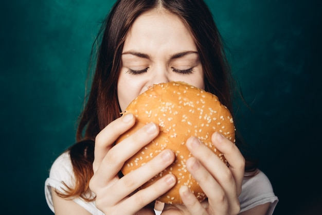 Szczęśliwa kobieta je hamburger, studio