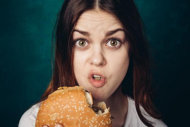 Szczęśliwa kobieta je hamburger