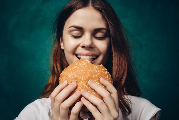 Szczęśliwa kobieta je hamburgera,