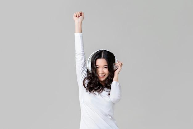 Szczęśliwa kobieta jest ubranym hełmofon słucha muzyka i taniec