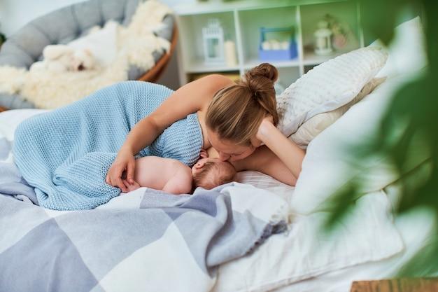 Szczęśliwa kobieta karmiąca, całująca i tuląca dziecko laktacja noworodka koncepcja