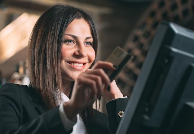 Szczęśliwa kobieta, kelner lub kierownik w fartuchu przy kasie z kasą pracującą w barze lub kawiarni