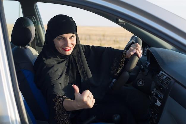 Szczęśliwa kobieta kierowca uśmiecha się podczas jazdy pokazuje kciuk w górę.,