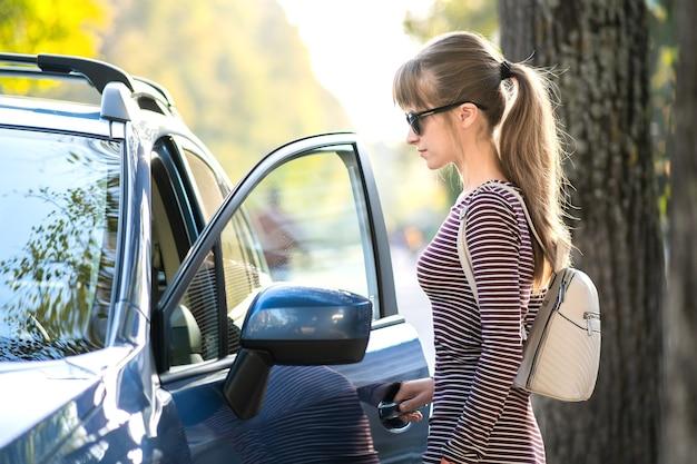 Szczęśliwa kobieta kierowca w dorywczo strój, ciesząc się ciepły dzień w pobliżu jej samochodu na letniej ulicy.