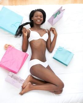 Szczęśliwa kobieta kłama na łóżku otaczającym z torba na zakupy