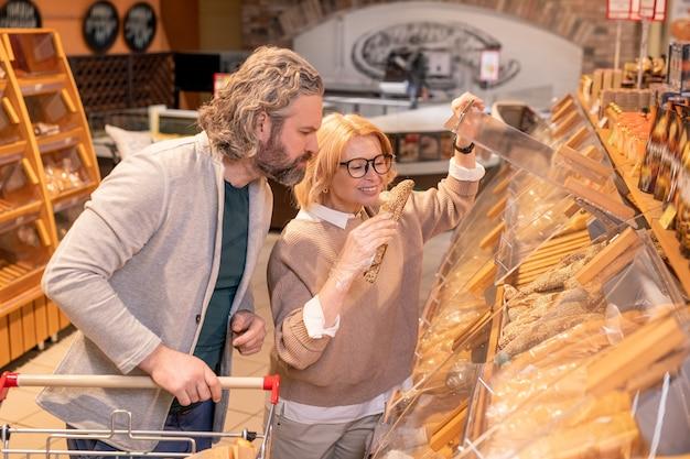 Szczęśliwa kobieta klient biorąc świeży chleb z drewnianego wyświetlacza podczas kupowania produktów spożywczych z mężem w supermarkecie