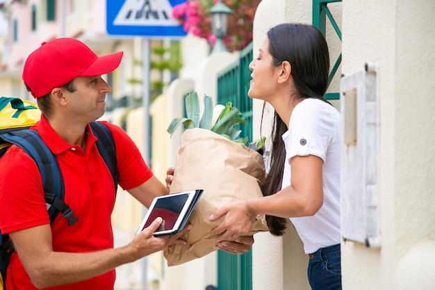 Szczęśliwa kobieta klient odbiera jedzenie ze sklepu spożywczego, biorąc paczkę od kuriera przy jej bramie. koncepcja usługi dostawy lub dostawy