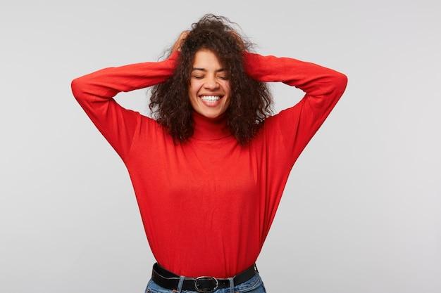 Szczęśliwa kobieta kobieta oczy zamknięte z przyjemności, trzyma obie ręce na głowie