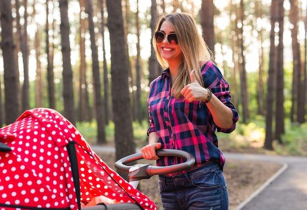 Szczęśliwa kobieta koncepcja macierzyństwa z wózkiem pokazując kciuk do góry na zewnątrz