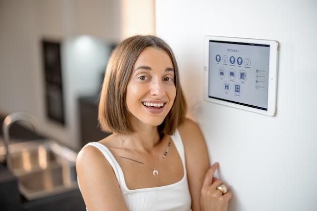 Szczęśliwa kobieta kontrolująca inteligentne urządzenia za pomocą panelu sterowania w kuchni