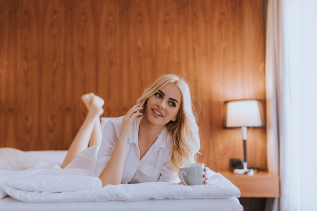 Szczęśliwa kobieta korzysta z telefonu komórkowego leżąc na łóżku i pije poranną kawę w domu