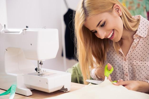 Szczęśliwa kobieta krawiec cięcia tkaniny