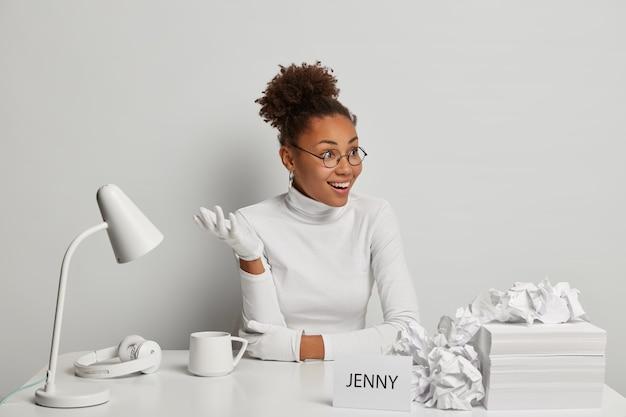 Szczęśliwa kobieta kręcone pozuje w przestrzeni coworkingowej, podnosi dłoń w białych rękawiczkach